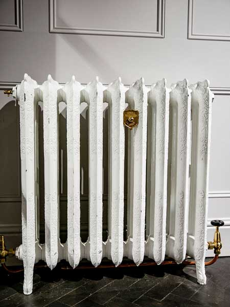 Cast Iron Radiator painted white with wall holder